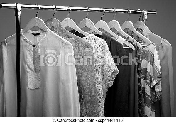 24f2cdbe586 Black and white photo of womens clothes on hangers. closet of wo ...