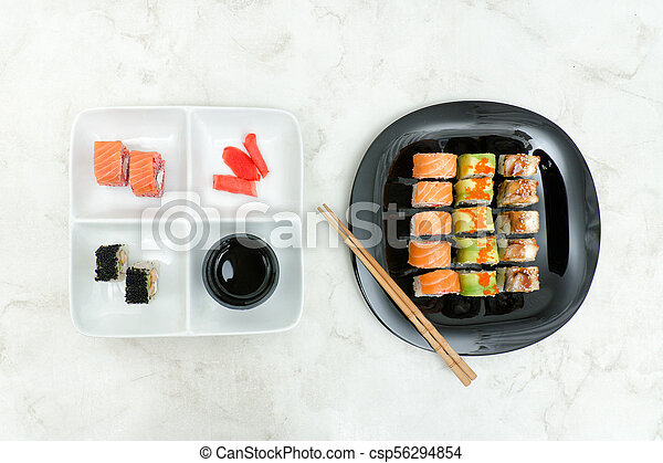 Black and white plate with various rolls and chopsticks. Top view - csp56294854