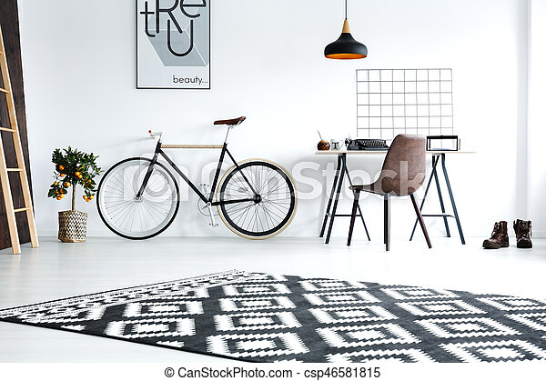 Black and white studio flat with pattern carpet, desk, chair