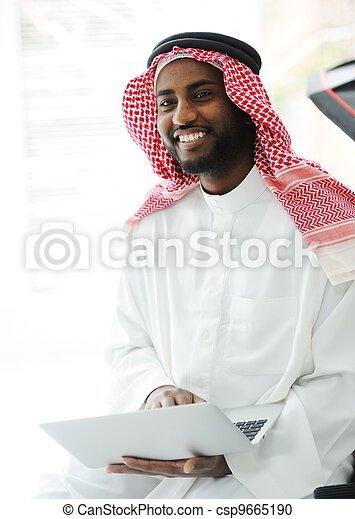 Black Arabic man working on laptop - csp9665190