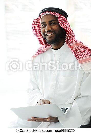 Black Arabic man working on laptop - csp9665320