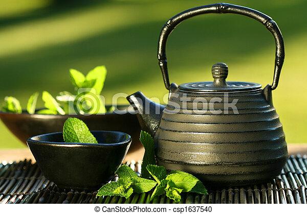 Black asian teapot with mint tea - csp1637540