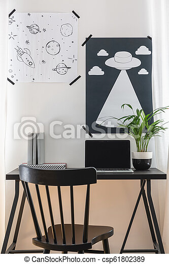 Black chair at desk with laptop and plant in home office interior with posters on white wall. Real photo - csp61802389