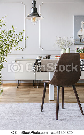 Black chair on grey carpet at table in dining room interior with lamp and wall with molding. Real photo - csp61504320
