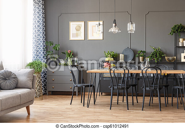 Black chairs at wooden dining table in grey living room interior with couch and posters. Real photo - csp61012491