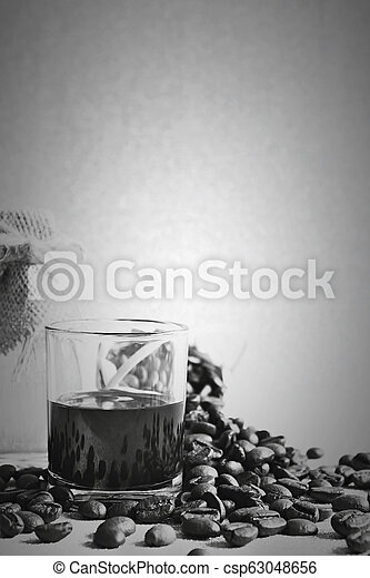 Black coffee cup and Coffee beans and Honey in the bottleon on golden background. - csp63048656