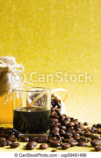 Black coffee cup and Coffee beans and Honey in the bottleon on golden background. - csp59491496