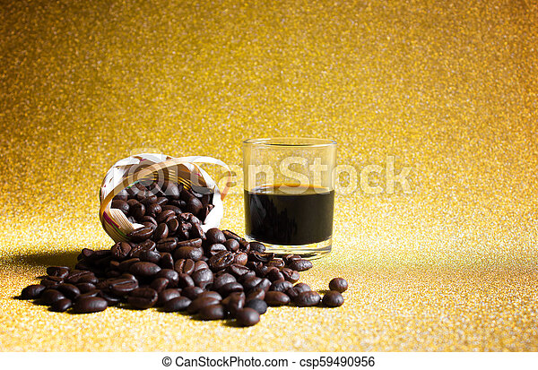 Black coffee cup and Coffee beans on golden background. - csp59490956