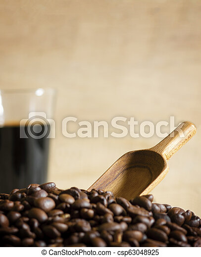 Black coffee cup and Coffee beans on wooden background. - csp63048925