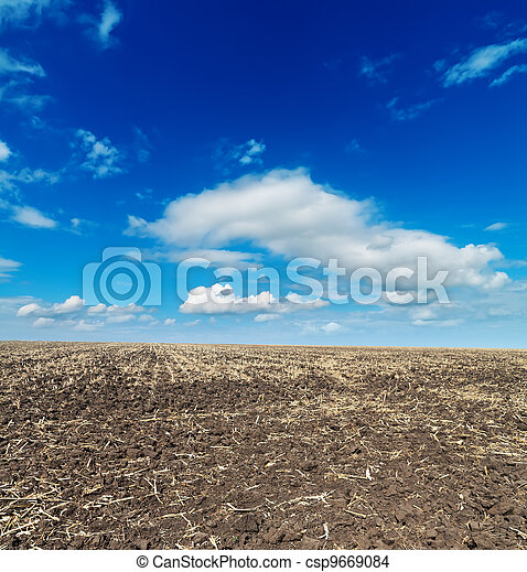 black cultivated field and blue sky - csp9669084