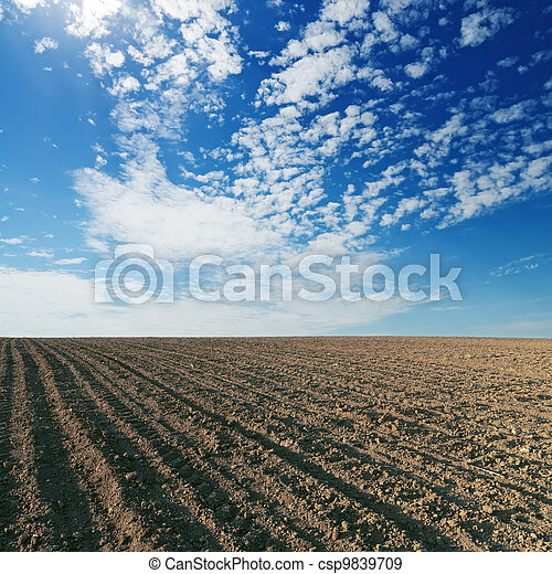 black cultivated field and blue sky - csp9839709