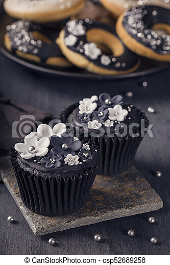 Black cupcakes on a wooden background - csp52689258