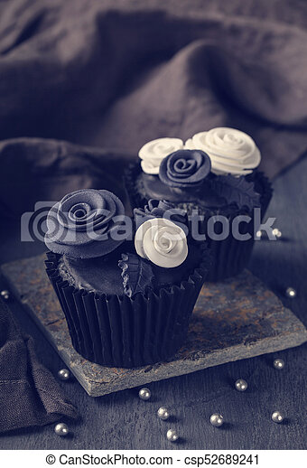Black cupcakes on a wooden background - csp52689241