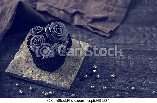 Black cupcakes on a wooden background - csp52689234