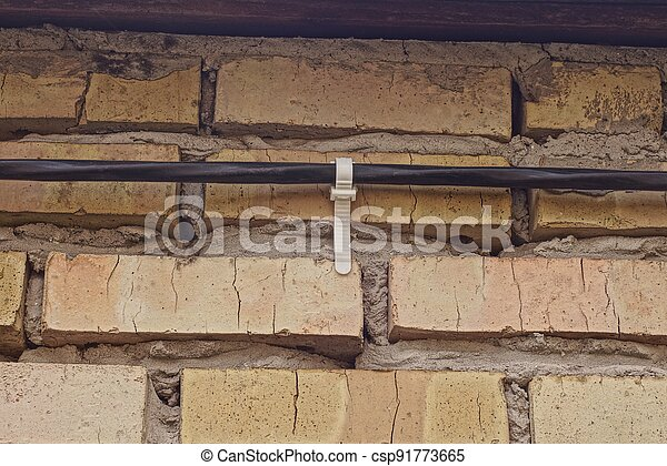 black electrical cable with white plastic fastener clamp on a brown brick wall - csp91773665