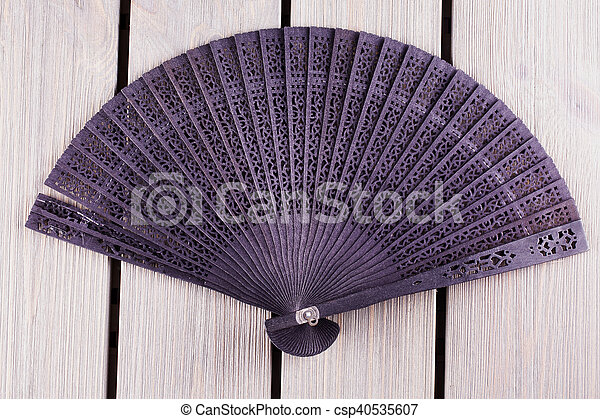 Black fan over wooden table - csp40535607
