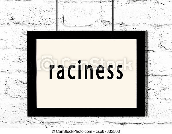 Black frame hanging on white brick wall with inscription raciness - csp87832508