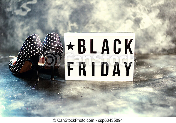 Black friday sale word on lightbox on dark table top view - csp60435894