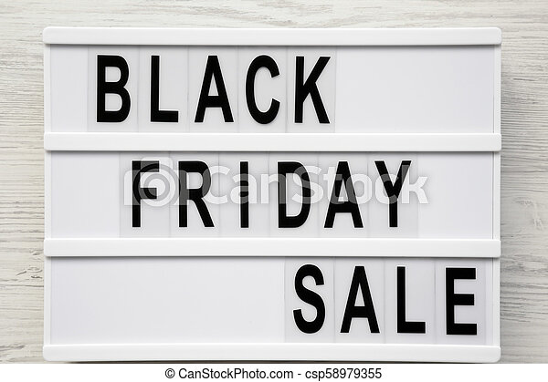 'Black friday sale' word on lightbox over white wooden surface, top view. From above, overhead. - csp58979355