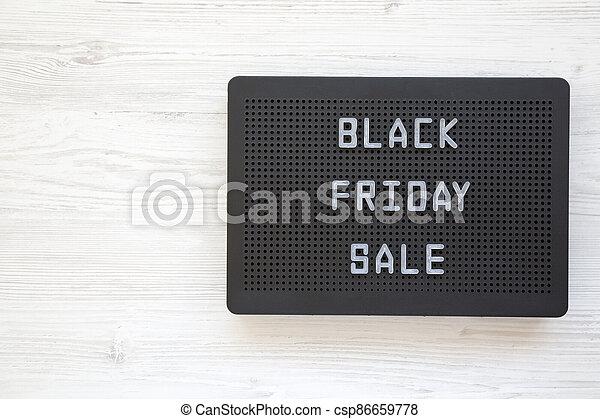 'Black Friday Sale' words on a black lightbox on a white wooden background, top view. From above, overhead. Copy space. - csp86659778