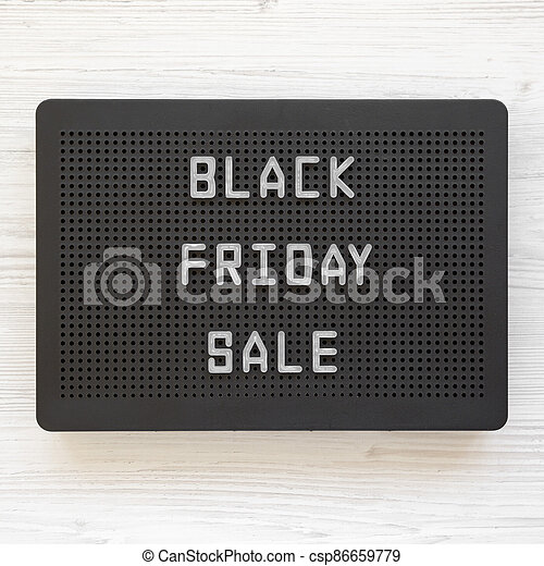 'Black Friday Sale' words on a black lightbox on a white wooden background, top view. From above, overhead, flat lay. - csp86659779