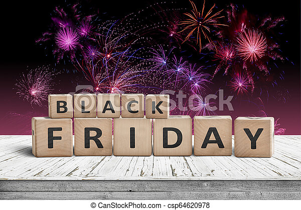 Black friday sign on a wooden table with fireworks - csp64620978