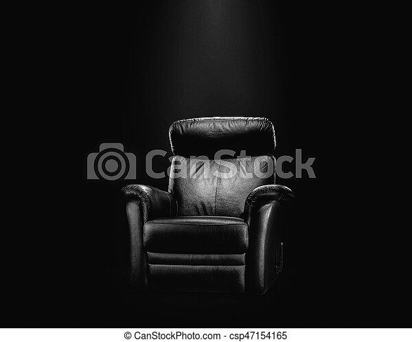 Black leather armchair in spotlight - csp47154165