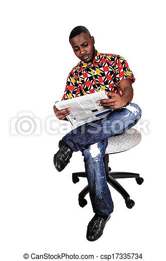 Black man reading paper. - csp17335734