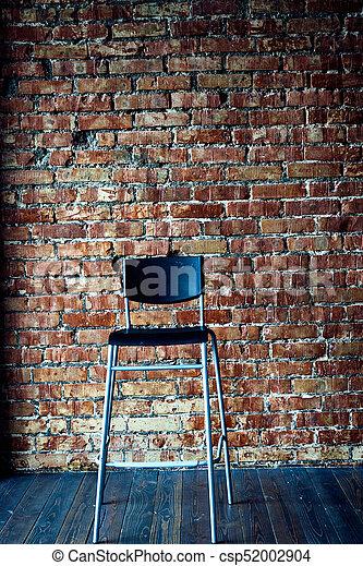 Black modern chair on brick wall background - csp52002904