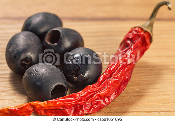 Black olives and dried red pepper on cutting board - csp61051695