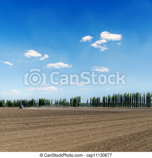 black ploughed field under blue sky - csp11130677
