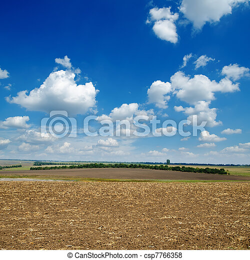 black ploughed field under blue sky - csp7766358