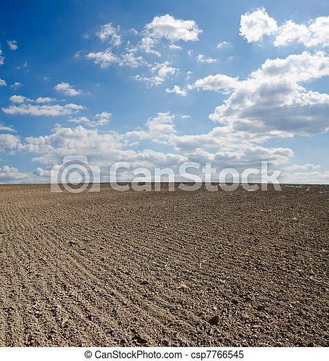 black ploughed field under blue sky - csp7766545