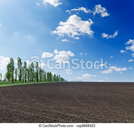 black plowed field under blue sky - csp9668423