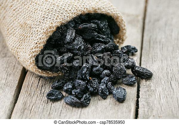 Black raisins in burlap bag over wooden gray table - csp78535950
