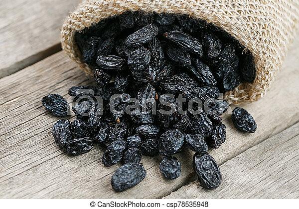Black raisins in burlap bag over wooden gray table - csp78535948