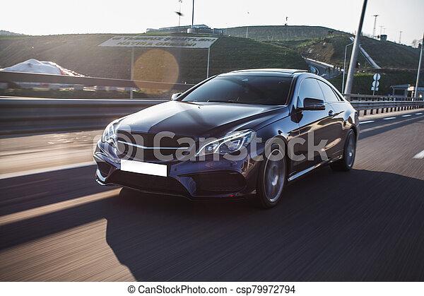 Black sedan car driving on the country road - csp79972794