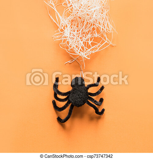 Black spider and web on orange. View from above. Minimal Halloween party decor. - csp73747342