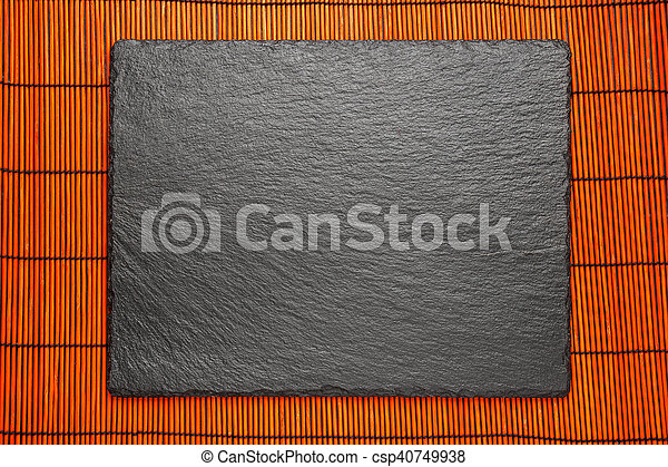 black stone plate on red bomboo mat background with copyspace top view