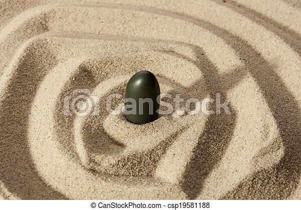Black stone sticking out of the sand  - csp19581188