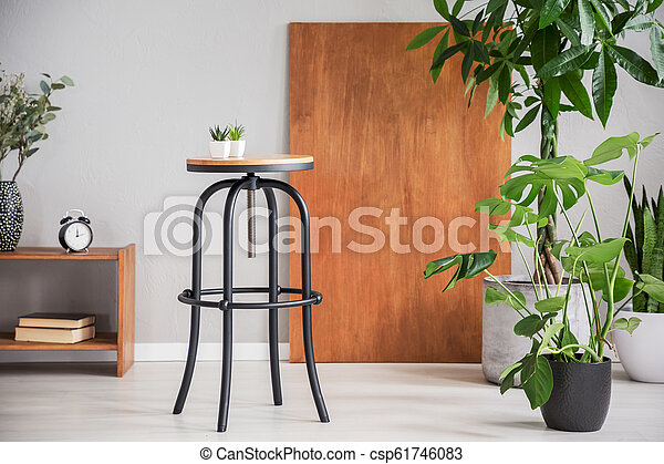 Black table between wooden cabinet and plants in grey living room interior with desk. Real photo - csp61746083