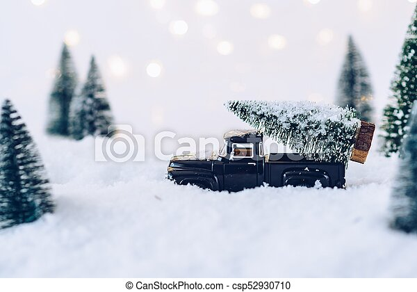 Black toy car carrying Christmas tree. - csp52930710