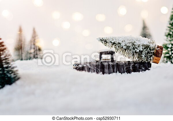 Black toy car carrying Christmas tree. - csp52930711