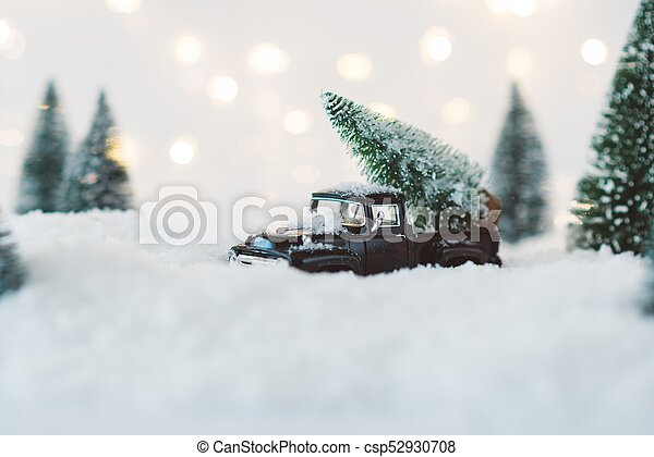 Black toy car carrying Christmas tree. - csp52930708