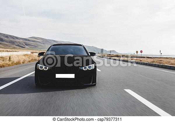 Black velvet sport sedan on the road - csp79377311