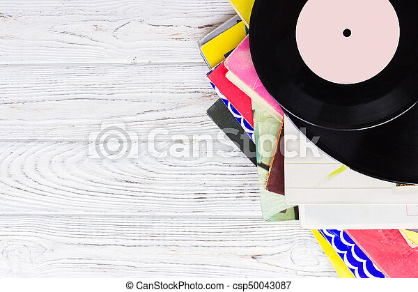 Black vinyl records on the wooden table, selective focus with copy space. Top view - csp50043087
