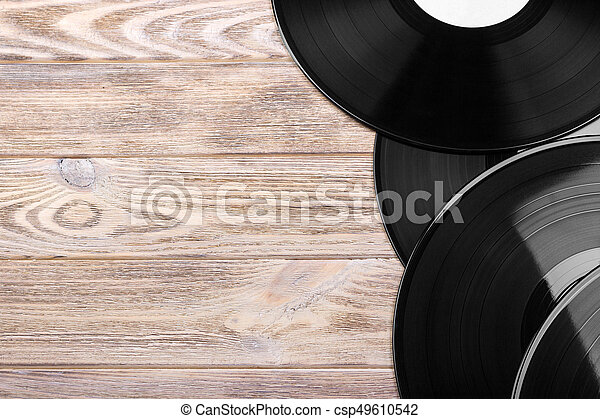 Black vinyl records on the wooden table, selective focus with copy space. Top view - csp49610542