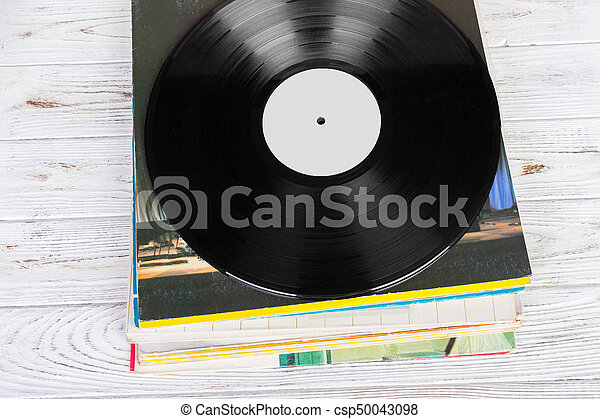 Black vinyl records on the wooden table, selective focus with copy space. Top view - csp50043098