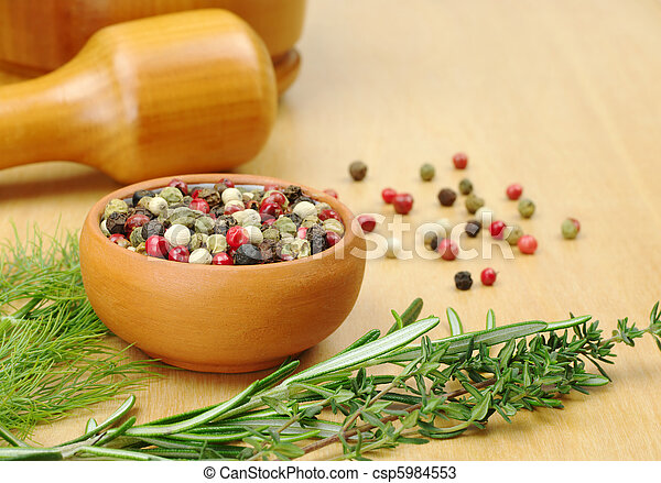 Black, white, green and red pepper corns in a ceramic bowl with other herbs (rosemary, dill, thyme) in the foreground and a mortar and pestle in the background (Selective Focus, Focus on the front of  - csp5984553