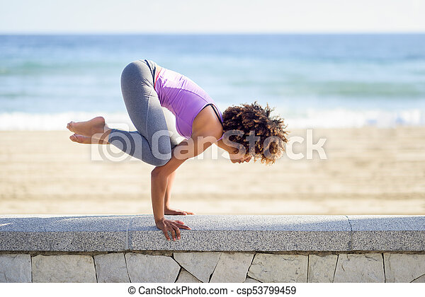 black woman afro hairstyle doing yoga in the beach young female